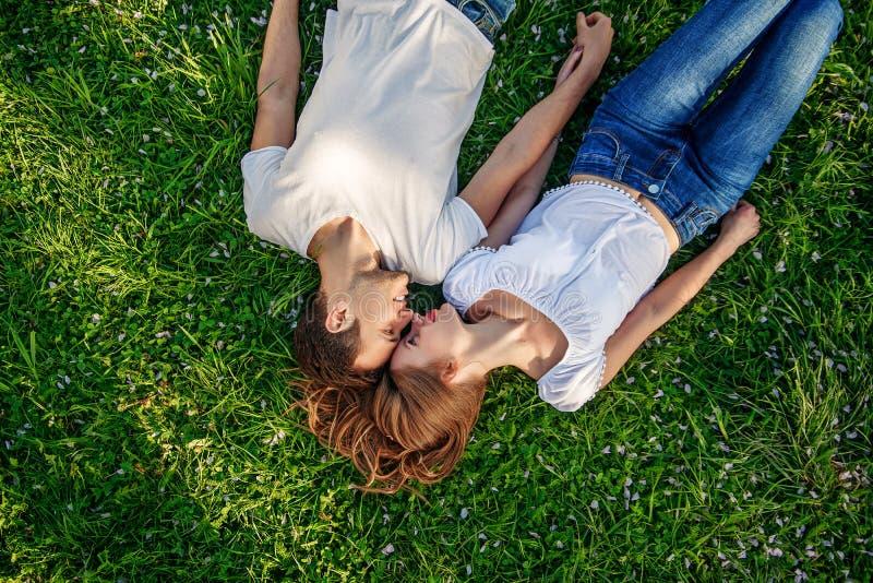 Pares românticos de jovens que encontram-se na grama no parque Colocam nos ombros de se e mantêm as mãos unidas imagens de stock royalty free