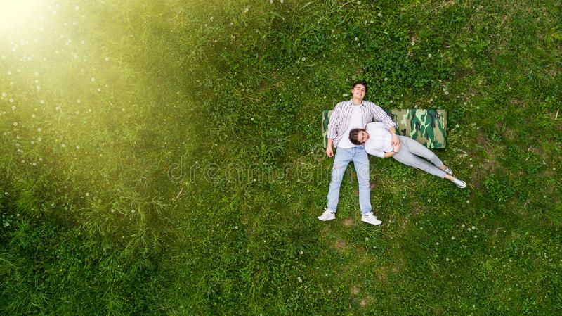 Pares românticos de jovens que encontram-se na grama no parque Colocam nos ombros de se e mantêm as mãos unidas Vista de fotos de stock royalty free