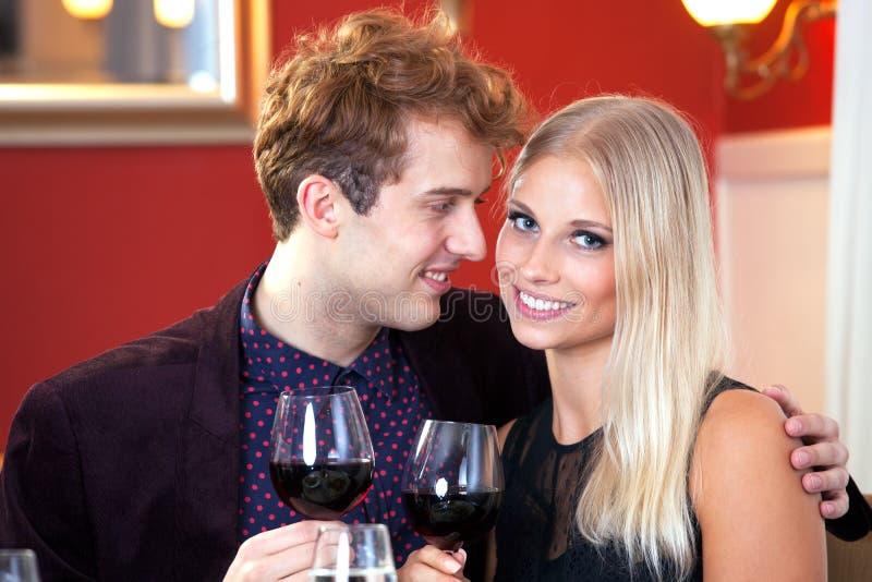 Pares românticos de sorriso que comem o vinho imagens de stock royalty free