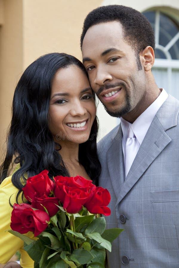 Pares românticos do americano africano com rosas fotos de stock royalty free