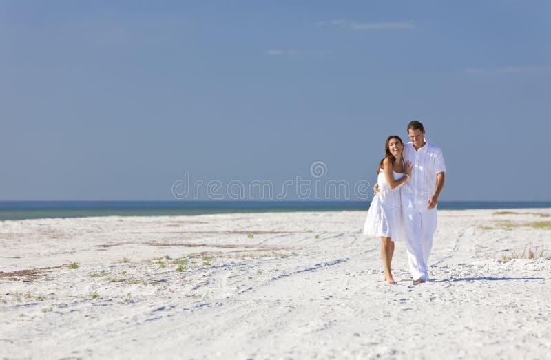 Pares românticos do homem & da mulher que andam em uma praia fotos de stock