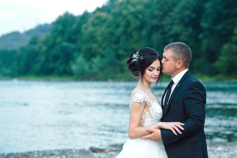 Pares românticos do recém-casado que abraçam perto do lago azul, noiva lindo de abraço do noivo sensual de trás perto do rio Dia  fotos de stock