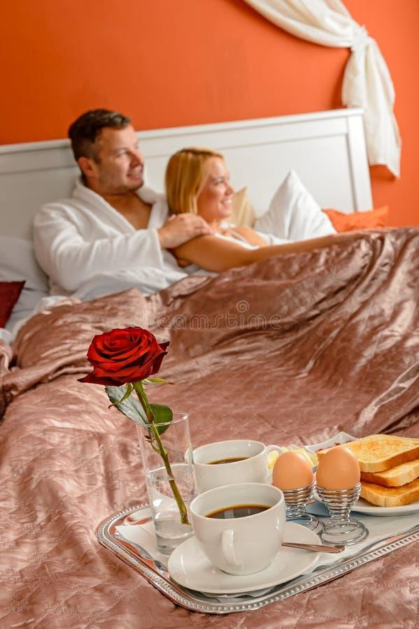 Pares românticos dos jovens do serviço de sala do hotel do pequeno almoço imagem de stock