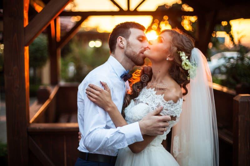 Pares românticos dos valentynes de recém-casados que abraçam no beijo no por do sol perto de uma casa de madeira fotos de stock royalty free