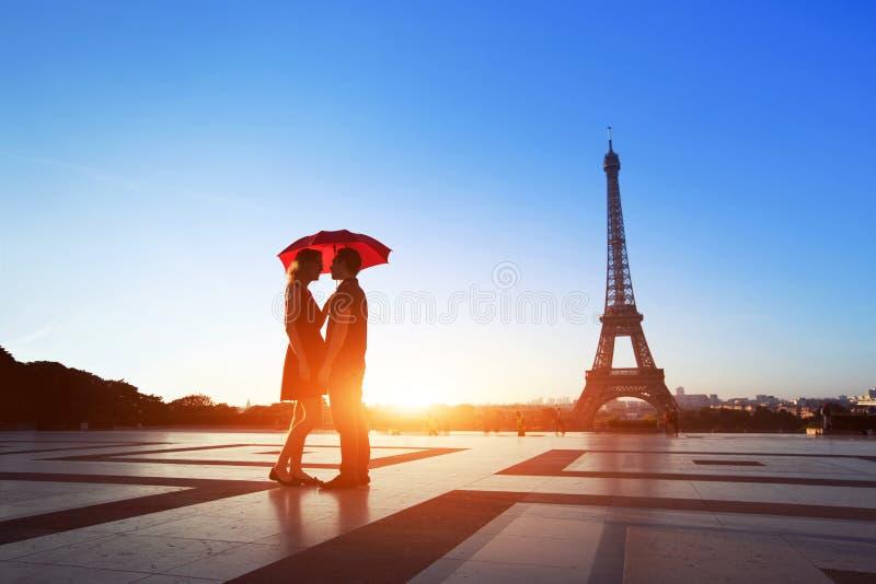 Pares românticos em Paris, em homem e em mulher sob o guarda-chuva perto da torre Eiffel imagem de stock