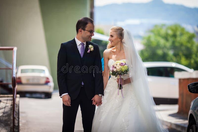 Pares românticos felizes de recém-casados que guardam as mãos foto de stock