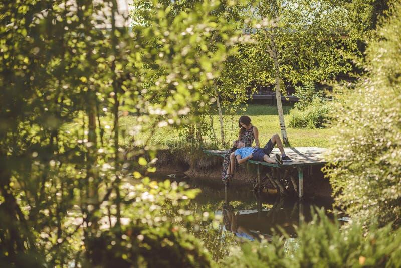 Pares românticos felizes na vila, caminhada na ponte de madeira perto do lago O homem no regaço de uma jovem mulher fotografia de stock