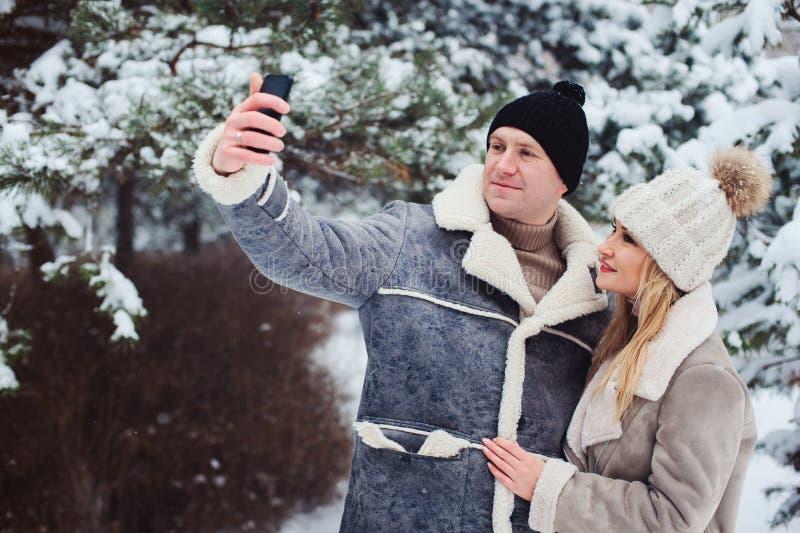 pares românticos felizes que fazem o selfie exterior no inverno nevado fotos de stock royalty free