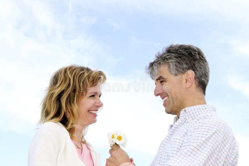Pares românticos maduros com flores fotografia de stock royalty free