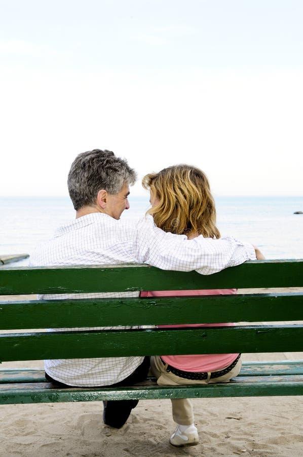 Pares românticos maduros em um banco imagens de stock