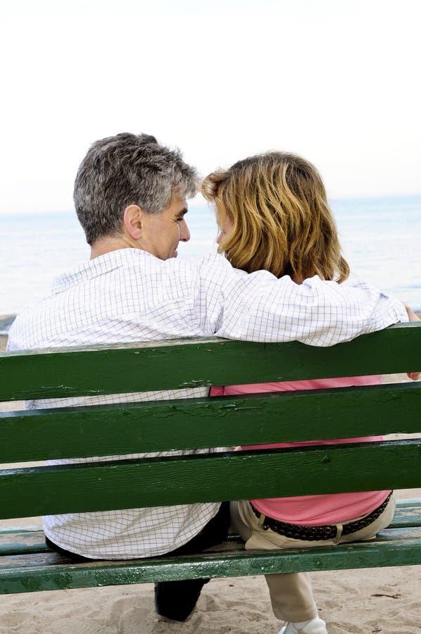 Pares românticos maduros em um banco foto de stock