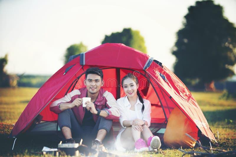 Pares românticos na barraca no local de acampamento fotografia de stock