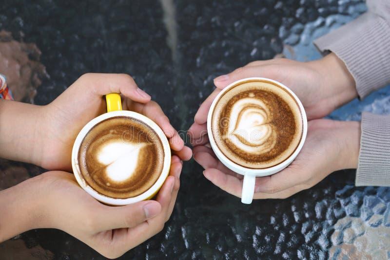 Pares românticos na mão do amor que guarda dois copos da arte do latte com teste padrão o coração na tabela na cafetaria fotos de stock