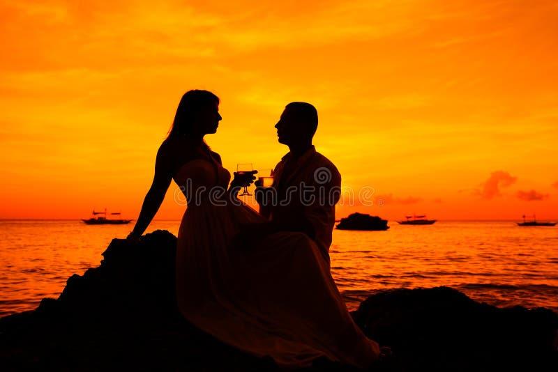 Pares românticos na praia tropical com por do sol no fundo fotografia de stock