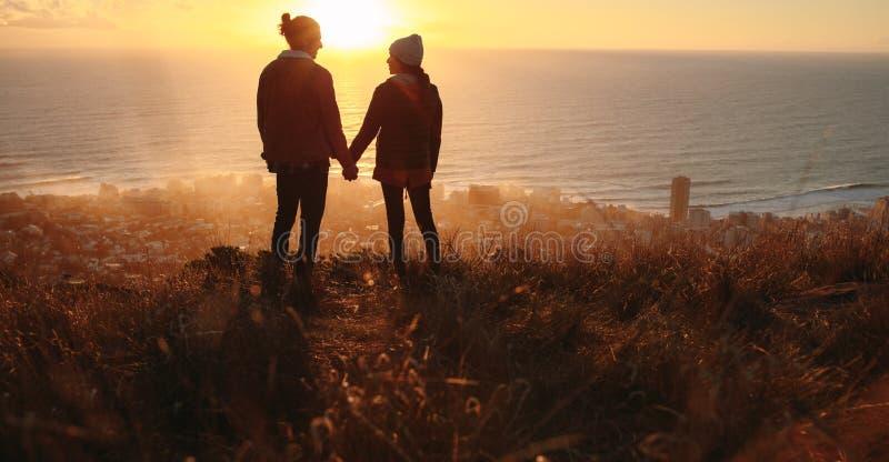 Pares românticos no pico no por do sol fotografia de stock
