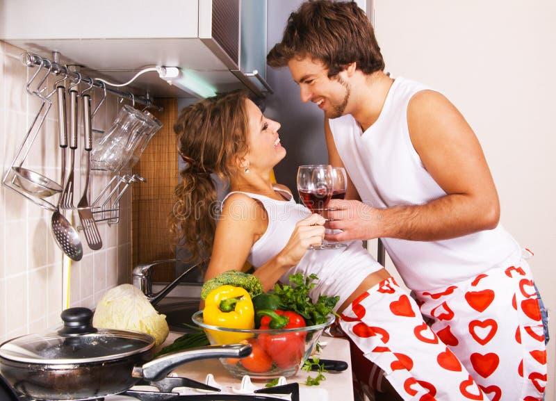 Pares românticos novos na cozinha imagens de stock