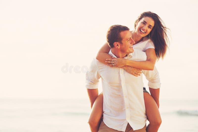 Pares românticos novos que jogam na praia imagem de stock