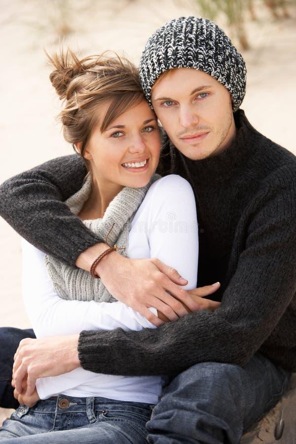 Pares românticos novos que relaxam na praia junto foto de stock