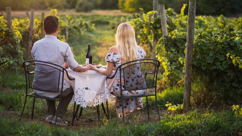 Pares românticos novos que sentam-se em uma tabela com o vinho e os petiscos, admirando o vinhedo Jantar romântico fotografia de stock