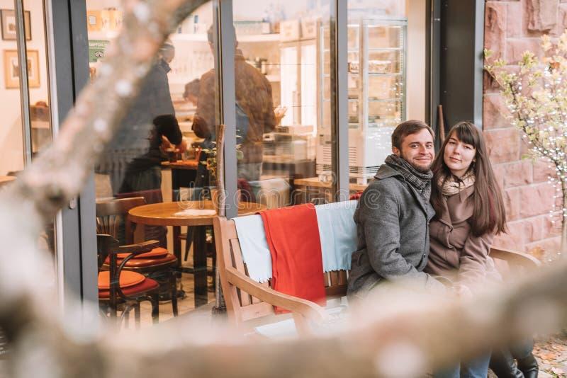 Pares românticos novos que sentam-se no banco imagens de stock royalty free