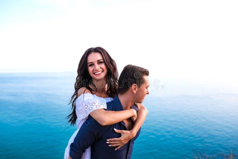 Pares românticos que abraçam a American National Standard que sorri no por do sol foto de stock royalty free