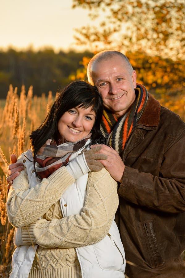 Pares românticos que abraçam no parque do por do sol do outono fotografia de stock