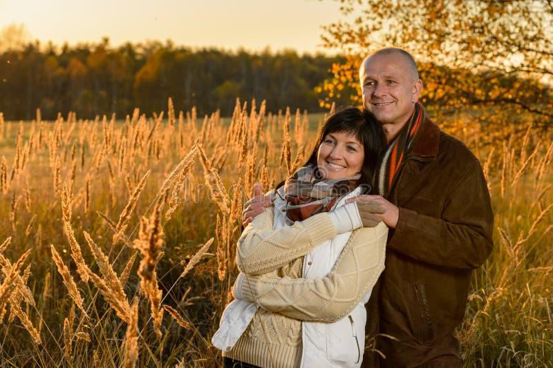 Pares românticos que abraçam no por do sol do outono do campo imagens de stock