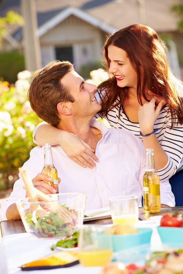 Pares românticos que apreciam a refeição exterior no jardim imagem de stock