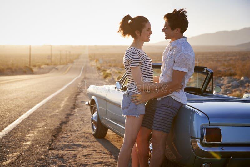 Pares românticos que apreciam a viagem por estrada no carro clássico imagem de stock
