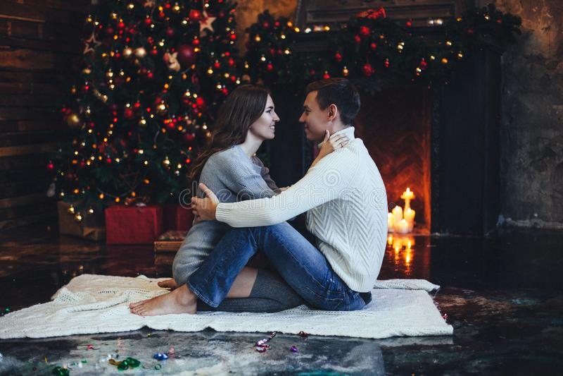Pares românticos que beijam perto da árvore e da chaminé de Natal em casa em camisetas confortáveis na noite fotos de stock