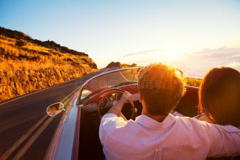 Pares românticos que conduzem na estrada bonita no por do sol fotografia de stock royalty free