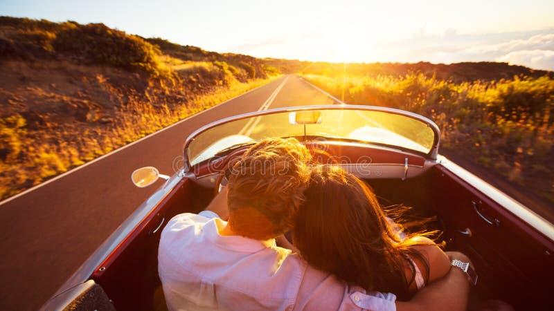 Pares românticos que conduzem na estrada bonita no por do sol fotos de stock royalty free