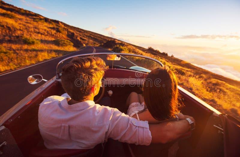 Pares românticos que conduzem na estrada bonita no por do sol foto de stock