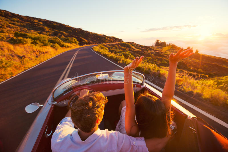 Pares românticos que conduzem na estrada bonita no por do sol imagem de stock royalty free