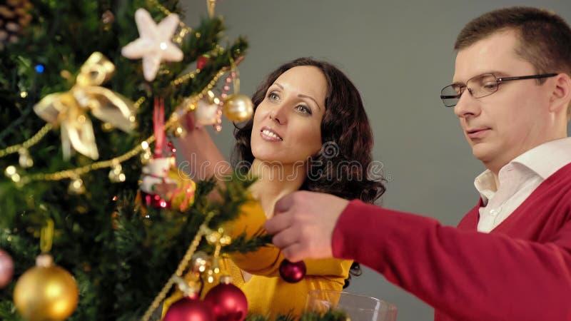 Pares românticos que decoram a árvore de Natal, apreciando o passatempo mútuo em casa fotografia de stock