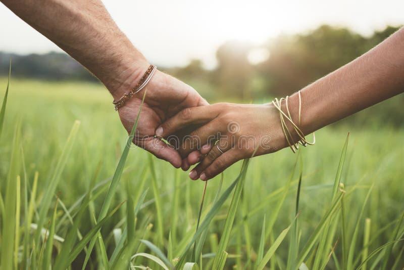 Pares românticos que guardam as mãos em um campo foto de stock royalty free