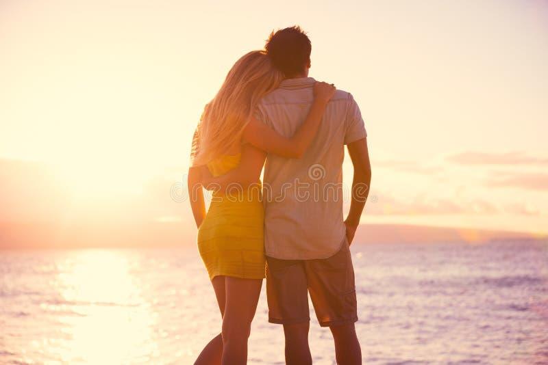 Pares românticos que olham o por do sol na praia tropical fotos de stock royalty free