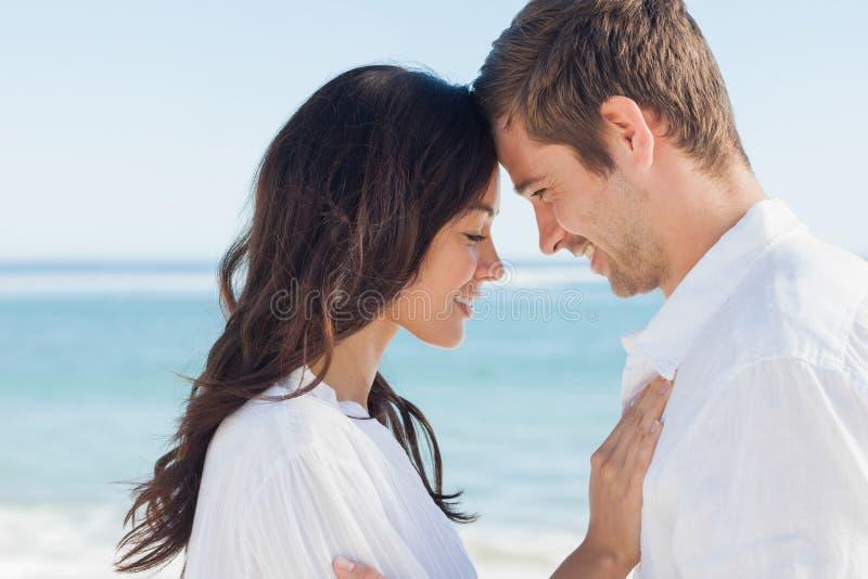 Pares românticos que relaxam e que abraçam na praia fotografia de stock royalty free