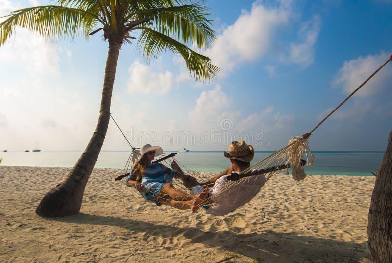 Pares românticos que relaxam na rede da praia em Maldivas imagem de stock