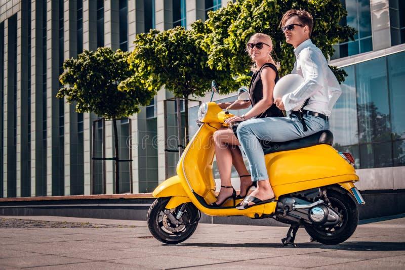 Pares românticos que sentam-se em um 'trotinette' italiano clássico na rua de uma parte moderna de uma cidade europeia fotos de stock