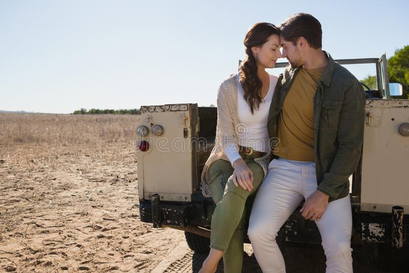 Pares românticos que sentam-se fora do veículo de estrada na paisagem fotos de stock