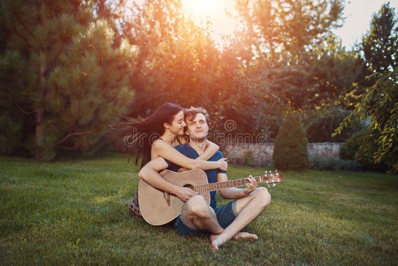 Pares românticos que sentam-se na grama no jardim imagens de stock royalty free