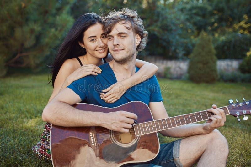 Pares românticos que sentam-se na grama no jardim foto de stock