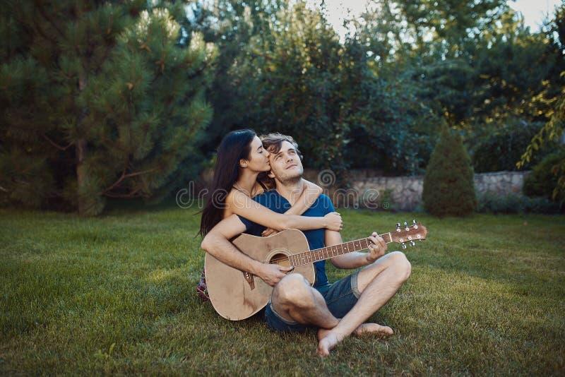 Pares românticos que sentam-se na grama no jardim foto de stock royalty free