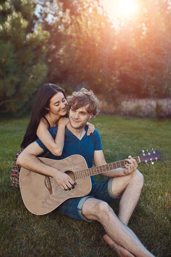 Pares românticos que sentam-se na grama no jardim fotos de stock royalty free