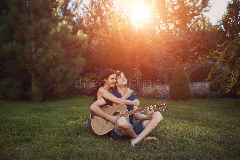 Pares românticos que sentam-se na grama no jardim imagem de stock