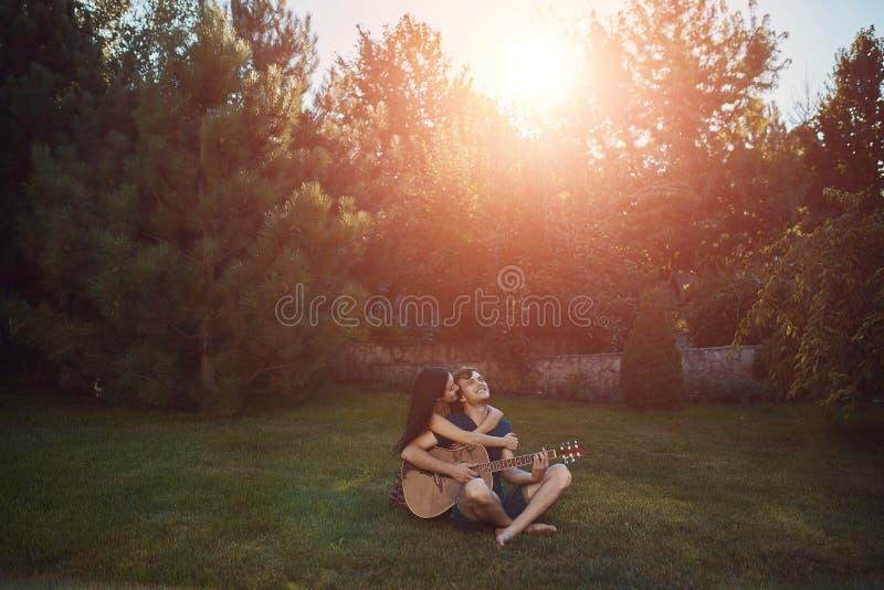 Pares românticos que sentam-se na grama no jardim fotografia de stock royalty free