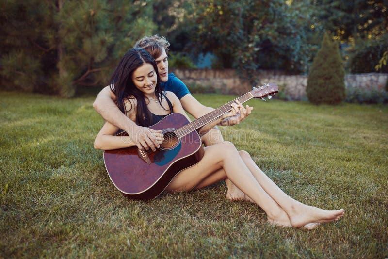 Pares românticos que sentam-se na grama no jardim imagens de stock
