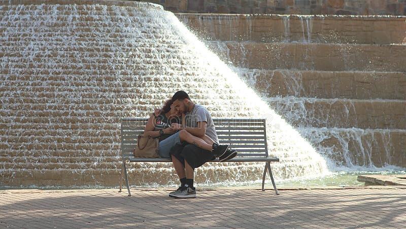 Pares românticos que sentam-se no banco perto da fonte em Riverwalk em San Antonio imagem de stock royalty free