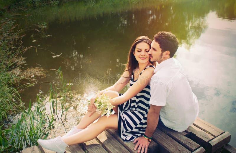 Pares românticos sensuais no amor no cais no lago no dia ensolarado foto de stock